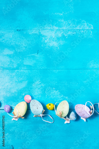 Fotobehang Zuivelproducten Easter eggs row on blue background with copy space