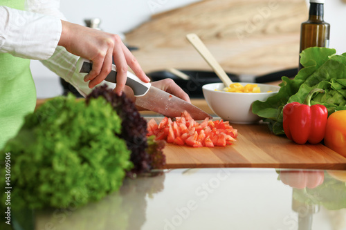 Poster Cuisine Closeup of human hands cooking vegetables salad in kitchen on the glass table with reflection. Healthy meal and vegetarian concept