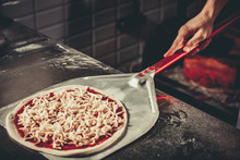 Food Concept. Preparing Traditional Italian Pizza. Chef Holds Long Irob Shovel For Pizza, Baking Dough With Pasta And Cheese In A Professional Oven. Only Hands Close Up