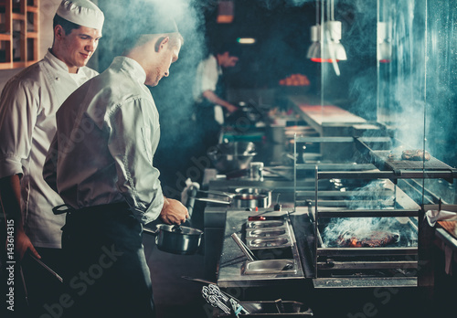 Fototapeta Food concept. Chef in white uniform monitors the degree of roasting and greases meat with oil in saucepan in interior of modern restaurant kitchen. Preparing traditional beef steak on barbecue oven. obraz
