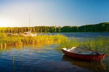 Fototapeta Rzeki i Jeziora Rowing boat and sailboats floating over the Lake Lasmiady waters early morning. Masuria, Poland.