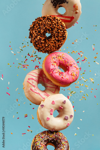 Various decorated doughnuts in motion falling on blue background.