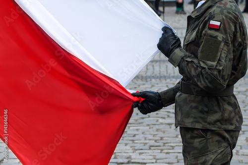 Plakat Polska flaga narodowa trzymana przez żołnierza podczas ceremonii