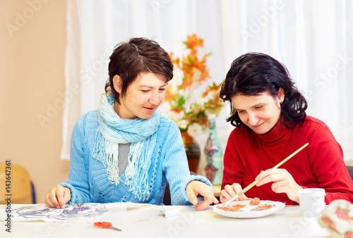 Photo adult woman with special needs are engaged in handcraft in rehabilitation center