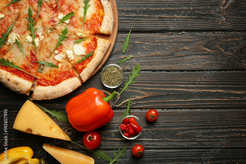Spoed Foto op Canvas Pizzeria Delicious pizza with ingredients on wooden table