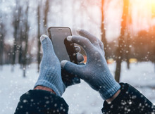 Man Using Smartphone In Winter With Gloves For Touch Screens