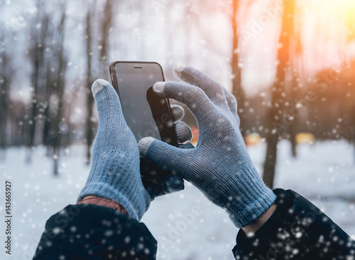 Fényképezés  Man using smartphone in winter with gloves for touch screens