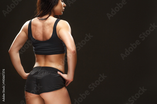 Excellent result. Cropped shot of a gorgeous muscular woman posing at the studio showing off her buttocks and back muscles on black backround.