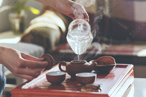 Staande foto Thee The tea ceremony. The woman pours hot water into the teapot
