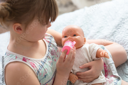 Fotografie, Tablou Kid girl playing with doll, feeding doll bottle