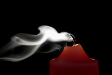 Smoke From A Red Candle On A B...