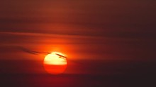 Vivid Red Sun Close Up Rising Above Cloud Layers On Hazy Morning.