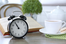 Retro Alarm Clock Showing Five Minutes To Eleven On Lunch Table