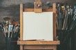 canvas print picture - Artistic equipment in a artist studio: empty artist canvas on wooden easel and paint brushes Retro toned photo.