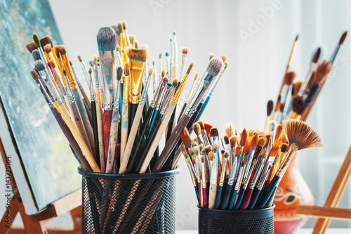 Artistic equipment in studio: wooden easel, paintbrushes, tubes of paint, palette and paintings on work artist table.