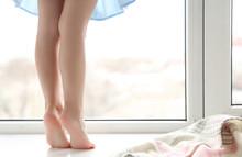 Legs Of Little Girl Standing On Windowsill