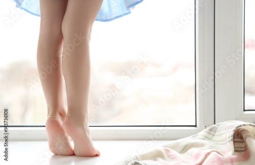 Valokuvatapetti Legs of little girl standing on windowsill