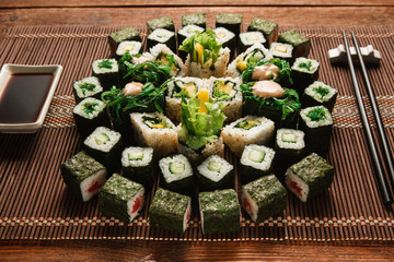 Sztuka kulinarna, tradycyjna kuchnia japońska. Okrągły ornament zestaw zielony rolek sushi serwowane na brązowy słomy mat, zbliżenie. Japońskie owoce morza, kulinarne arcydzieło.
