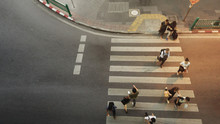People Walk On Pathway Pedestrian Crosswalk Of Top View City Street With Silhouette Shadow On The Ground At Night Time