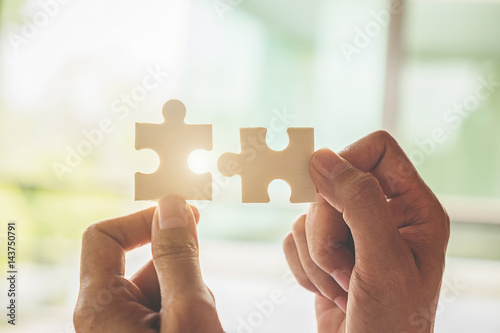 Fototapety, obrazy: Business woman hands connecting jigsaw puzzle. Business solutions, success and strategy concept. Close up photo with selective focus.