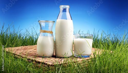 Plakat świeże mleko w szklanym dzbanku i szkła na świeżej zielonej trawie
