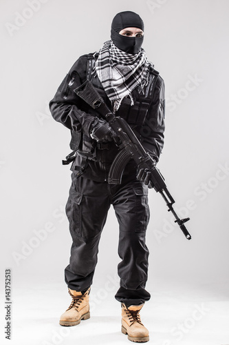 Photo Terrorist holding a machine gun in his hands isolated over white