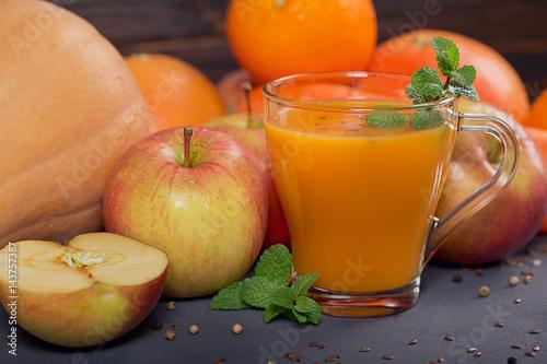 Fresh carrot, apple, pumpkin, orange, grapefruit on dark table.