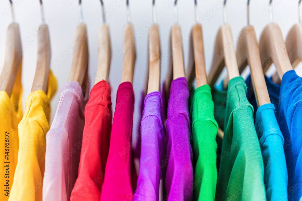 Fototapeta Fashion clothes on clothing rack - bright colorful closet. Closeup of rainbow color choice of trendy female wear on hangers in store closet or spring cleaning concept. Summer home wardrobe.