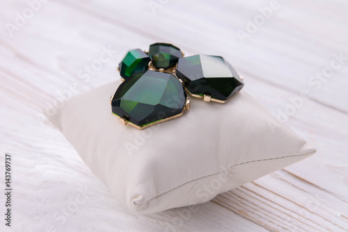 Fotografia  Gold earrings with emerald on the pillow