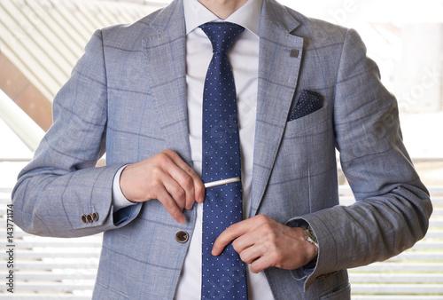 Fototapeta Unrecognizable businessman setting the tie straight obraz