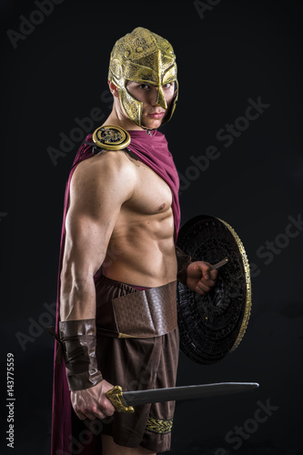 Young handsome muscular man posing in roman or spartan gladiator costume with shield and sword & Young handsome muscular man posing in roman or spartan gladiator ...