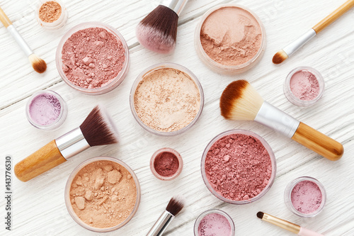 Fotografia Makeup powder and brushes on white wood flat lay