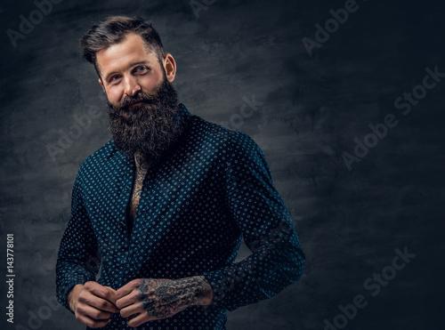 Bearded tattooed male dressed in dark blue jacket. Fototapeta