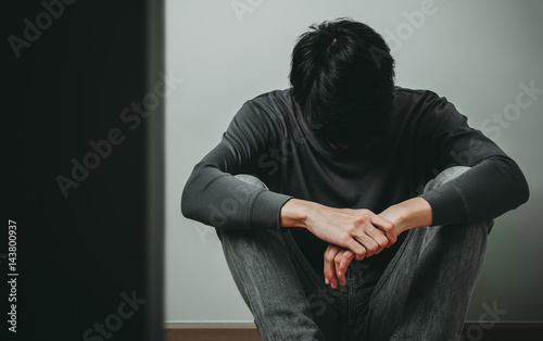 Despaired man hug his knee and cry when sitting alone on the floor behind the do Canvas Print