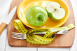 The concept of the diet. Green Apple lies on a plate, knife and fork wrapped in a centimeter on a wooden Board closeup