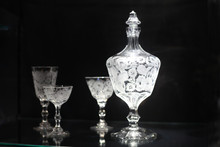 Glass Decanter With Shot Glasses On Black Background
