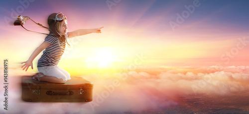 dziewczynka-na-walizce-w-podrozy-ponad-chmurami
