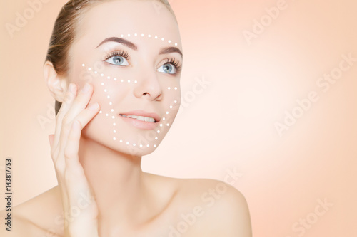 Fotografia  Woman face with marks and arrows on pink