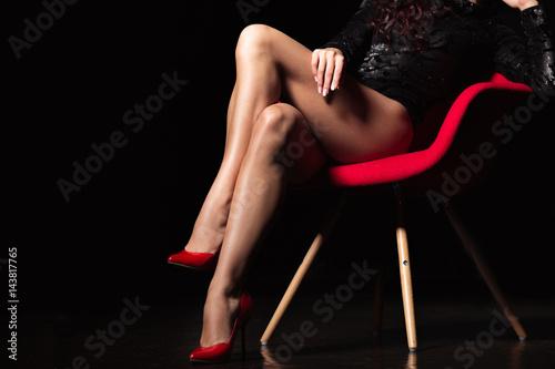 Zdjęcie XXL Idealne nogi kobiety na wysokich obcasach. Atrakcyjne, długie nogi młodej kobiety noszenia uwodzicielskiej bielizny pozowanie w zmysłowy sposób w ciemnym pokoju przez czerwone krzesło nowoczesne
