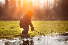 Little Boy Playing In Puddle At Springtime