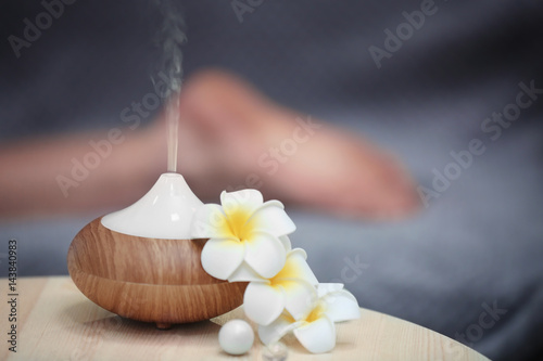 Türaufkleber Spa Spa concept. Aroma oil diffuser on table against blurred background