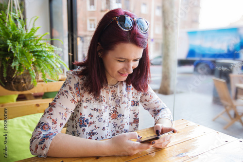 Fotomural  Young tourist woman using smartphone in restaurant waiting for her morning coffe