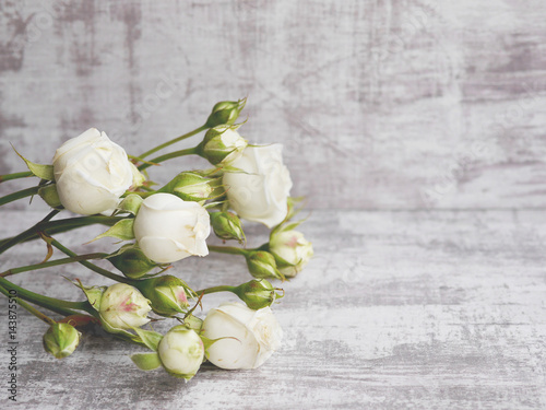 Fototapeta  Little white roses on a bleached board. Floral background.
