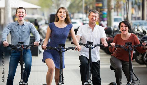 Valokuvatapetti Ordinary family of four with electrkc bikes