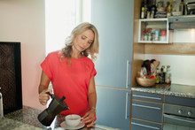 Woman Pouring Coffee Into Cup.