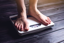 Women's Feet Are On Mechanical Scales For Weight Control