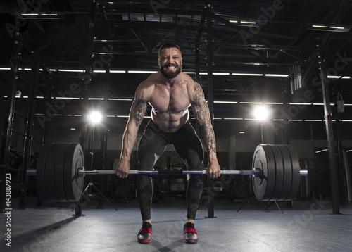 Fényképezés  Attractive muscular bodybuilder doing heavy deadlift exercise in
