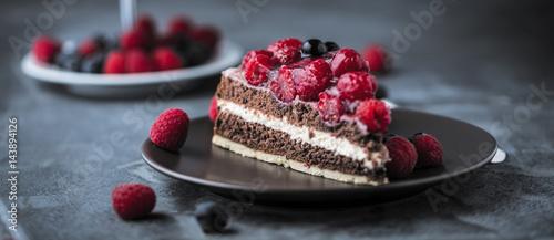 Vászonkép  Stück kuchen auf dunkelem hintergrund