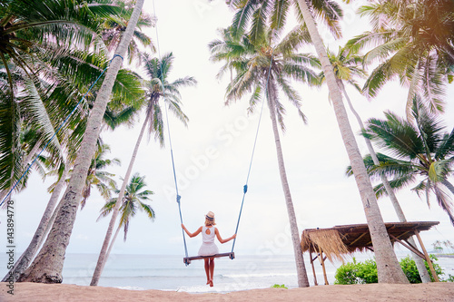 Montage in der Fensternische Bali Vacation concept. Happy young woman in white dress and hat swinging at palm grove enjoying sea view.