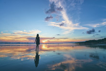 Sky And Sea. Beautiful Sunset. Silhouette Of Young Woman Walking On Ocean Beach.